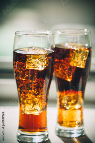 Fotografie, Obraz  Beautiful cold drink of Cola with ice cubes in a glass on a grey window background with free space