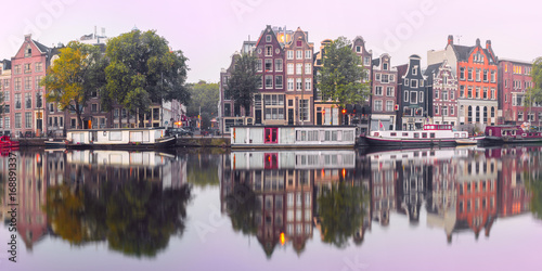Panorama of Amsterdam canal Amstel with typical dutch houses and houseboat from the boat in the morning, Holland, Netherlands Canvas Print