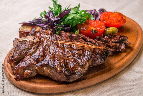 Appetizing steak on the bone, with tomatoes and herbs, on a wooden board. Horizontal frame