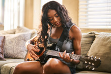 Woman Playing Guitar While Sit...