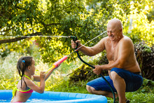 Grandfather And Granddaughter Pour Each Other With Water In An Inflatable Pool In The Garden Near The House