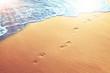 Leinwandbild Motiv Fußspuren im Sand am Strand