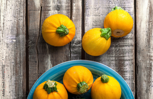 Yellow zucchini overhead group on blue plate and old rustic white wooden table in studio
