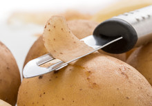 Potatoes, With A Vegetable Peeler On A White Background, Close Up