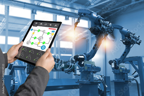 Fotografía  Engineer hand using tablet, heavy automation robot arm machine in smart factory industrial with tablet real time process control monitoring system application
