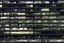 Multi-stories Office Building At Night With Worker Working Overtime. Late Night At Office.  Lighting And Working People Within. Late Night Overtime In A Modern Office Building