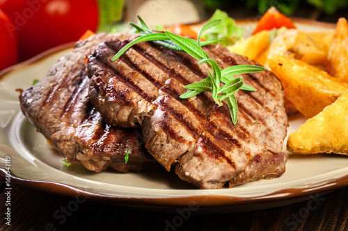 Papiers peints Steakhouse Succulent portions of grilled fillet mignon served with baked potatoes