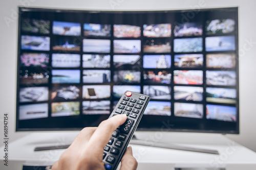 Fotografía  Hand pressing remote of smart tv