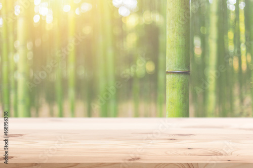 Foto  Wood foreground with blur bamboo wood forest background design for display natur