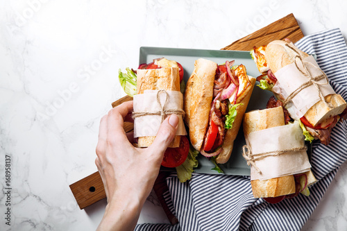 Recess Fitting Snack Fresh baguette sandwich bahn-mi styled. Bacon, roasted cheese, tomatoes and lettuce on metallic tray on white marble background. Female hand holding sandwich top view.