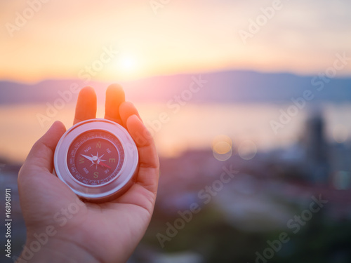 Fotografía  Closeup hand holding compass with  mountain and sunset sky background