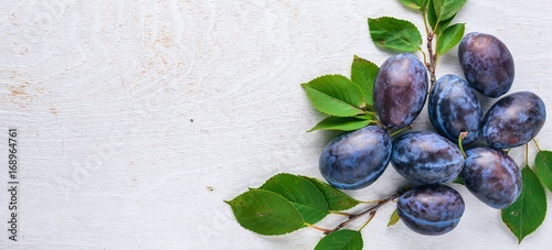 Plums with green leaves. On a wooden background. Top view. Free space for text.