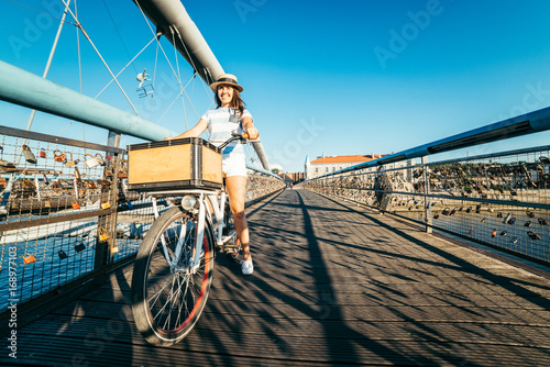 Fototapeta pretty woman riding bicycle on the bridge obraz