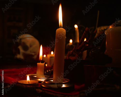 Fotografia, Obraz  Burning candles and human skull. Halloween and occult concept.