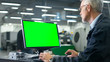 canvas print picture - Senior engineer in glasses is working on a desktop computer with a green screen on monitor in a factory.