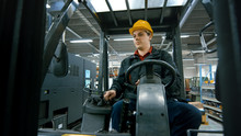 Portrait Of A Warehouse Worker Driving A Forklift Truck.