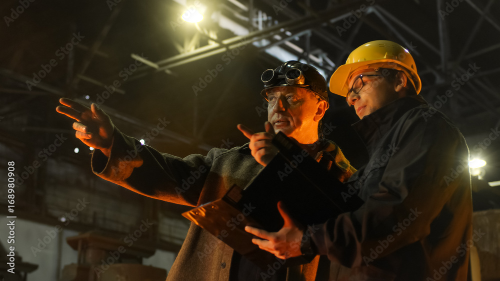 Fototapety, obrazy: Engineer and Worker Have Conversation in Foundry. Engineer Using Tablet. Rough Industrial Environment.