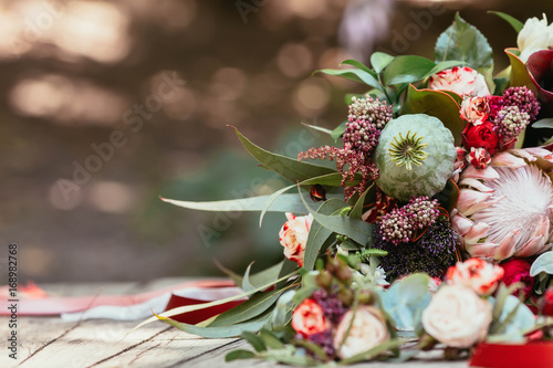 Fotografía  Rustic wedding bouquet with white and bordeaux roses, peonies, poppy and greens on an aged wooden floor