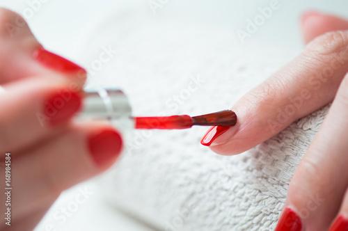 Obraz na płótnie Closeup of a woman painting her nails with red nail polish