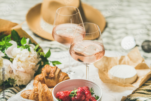 Foto auf Leinwand Picknick French style romantic summer picnic setting. Flat-lay of glasses of rose wine with ice, fresh strawberries, croissants, brie cheese, straw hat, sunglasses, peony flowers. Outdoor gathering concept
