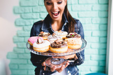 Beautiful Young Woman Enjoying In Delicious Glazed And Decorated Donuts