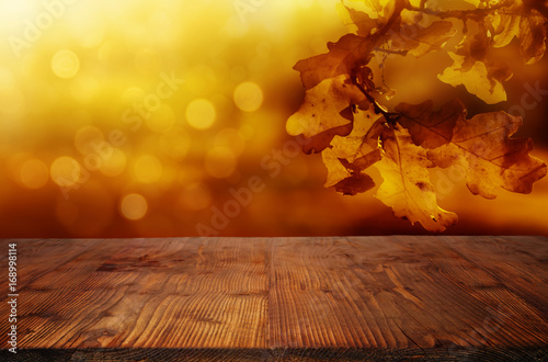 fototapeta na drzwi i meble Golden autumn leaves background with wooden table