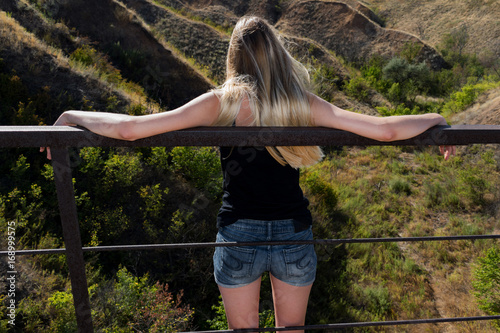 Canvas Depressed young girl thinks about suicide on the old rustic broken bridge