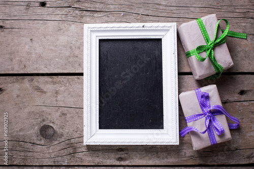 Empty blackboard and festive gift boxes with presents on aged wooden background.