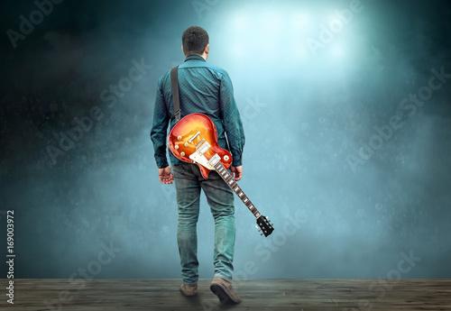 Fotografia, Obraz  Artist Guitarist hands play on electricity guitar under light, P
