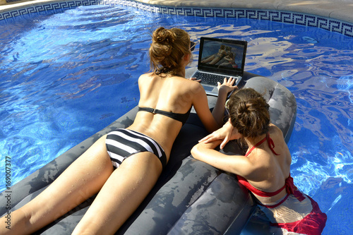Girls are  looking at the computer floating on airbed in a swimming pool Wallpaper Mural