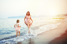 Young Joyful Female With Little Daughter Having Fun In The Sea.