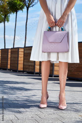 Beautiful slender legs tanned skin is shod in high-heeled shoes depilation body care catologue stylish fashion collection walks on the street health body care cream white dress bag.