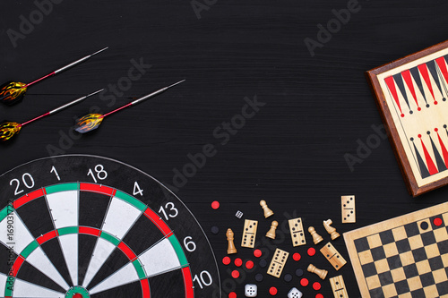 Photo  darts, backgammon, chess and dominoes on a black table top view
