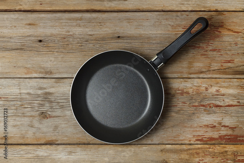 Empty frying pan on a wooden table, top view, rural style