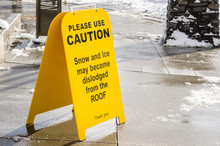 Sign On A Sidewalk Warning Pedestrian Of The Possibility That The Snow May Fall From The Roof