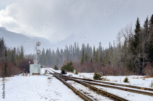 Valokuva  Switch and Signal along a Snowy Railroad in the Mountains on a Foggy Winter Day