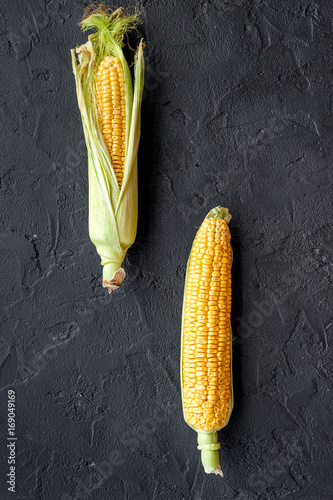 Ripe corn on cobs on black stone background top view Poster
