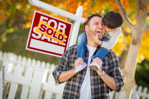 Fototapeta  Young Mixed Race Chinese and Caucasian Father and Son In Front of Sold For Sale Real Estate Sign and Fall Yard