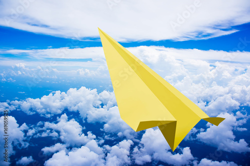 yellow-paper-plane-flying-against-blue-sky