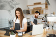 Coffee Business Concept - beautiful caucasian bartender barista or manager Posting order in digital tablet menu at modern coffee shop.