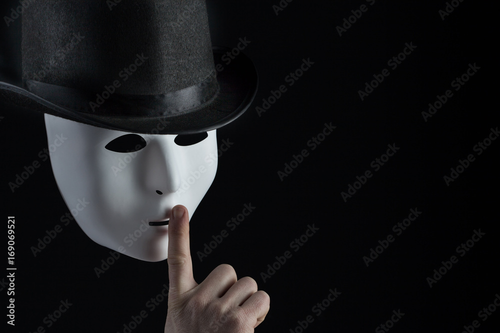 Fototapeta Male finger showing shh sign on white mask wearing black top hat on black background with copy space. Freedom of speech and silence concept