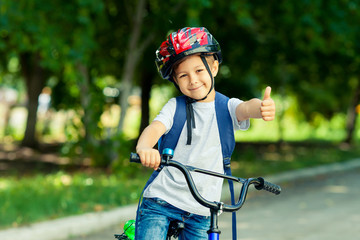 Fototapeta Little boy learns to ride a bike in thepark near the home. Kid shows the thumbs up on bicycle. Happy smiling child in helmet riding a cycling.