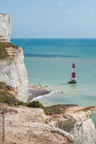 Fotografie, Obraz  Red and white Beachy Head lighthouse in blue sea English Channel under Seven Sis