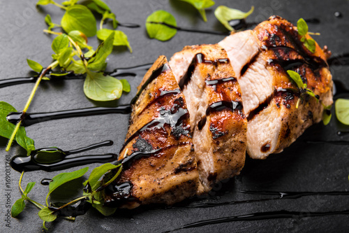 Roasted Chicken Breast on a Black Stone Plate with Balsamic Vinegar and Oregano