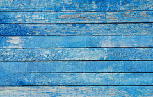 Fragment Of An Old Fence. Cracked Azure Paint Texture. Light Blue Wooden Planks Background.
