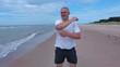 Man warm up before running near sea