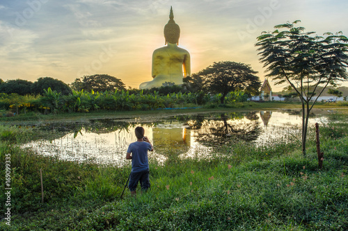 Photo Photographer take a photo with big buddha in wat muang background at Ang Thong Province popular buddhist shrine in Thailand