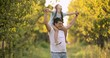 Family walks in the garden, Young girl on fathers shoulders. Slow motion