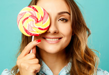 Young Pretty Smiley Woman Holding Lollipop In Hands Over Blue Background