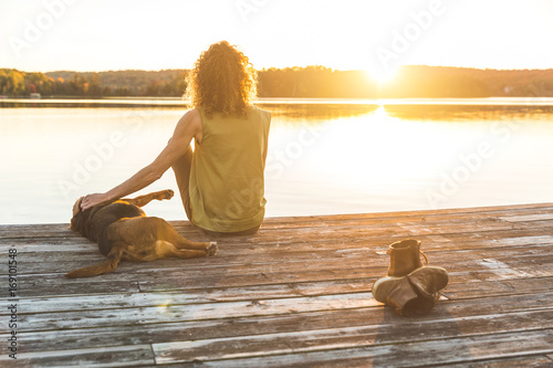 Woman and dog relaxing on the dock at sunset Canvas Print
